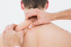 Rear view of a man being massaged by a physiotherapist Royalty Free Stock Photos