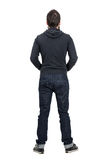 Rear view of man in black hooded shirt with rolled up jeans. Full body length portrait isolated over white studio background Stock Photo