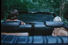 Rear view of man and boy driving through woods in convertible stock video footage