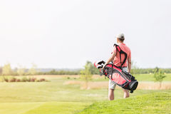 Rear view of man carrying golf club bag while walking at course royalty free stock photo