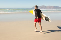 Rear view of man carrying surfboard while running on sand Royalty Free Stock Photos