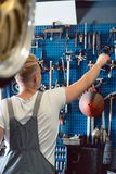 Rear view of a man choosing an useful tool during work in a repair shop. Rear view of a young man choosing an useful tool during work in a modern automobile Stock Photos