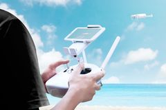 Rear view of man controlling white drone which flying over the beach with blue ocean stock photography