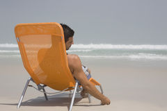 Rear View Of Man On Deckchair At Beach Stock Photos