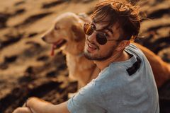 Rear view of a man and golden dog sitting on beach stock images