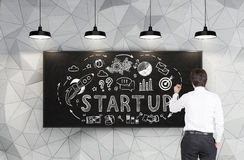 Rear view of man drawing startup icons on board Stock Photo