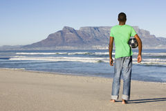 Rear View Of Man With Football At Table Mountain Beach Royalty Free Stock Images