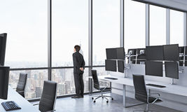 Rear view of a man in formal suit who is looking out the window in the modern panoramic office with New York view. White tables eq Stock Photography