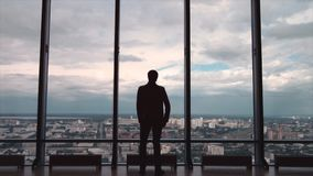 Rear view of man in formal suites who stand in front of panoramic window with city view. a man stands in front of big stock photo