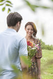 Rear view man giving flowers to woman in park Royalty Free Stock Photos