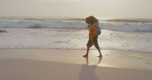 Side view of man giving piggyback ride to woman on the beach 4k. Rear view of man giving piggyback ride to woman on the beach. They are having fun 4k stock footage
