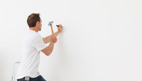 Rear view of a man hammering against a white wall Royalty Free Stock Photography