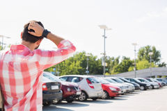 Rear view of man with hand behind head standing on city street against clear sky Stock Image