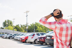Rear view of man with hand behind head standing on city street against clear sky Royalty Free Stock Images