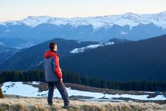 Male tourist enjoying beautiful panorama in the evening. Rear view of man hiker watching to beautiful panorama in the evening on the blurred background snow Stock Images