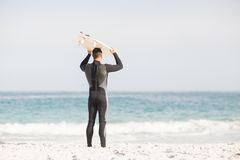 Rear view of man holding surfboard over head Stock Photo