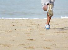 Rear view of man jogging at the beach Stock Images
