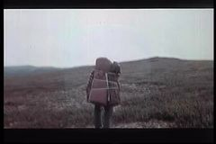 Rear view of man with large backpack hiking across mountain stock video footage
