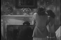 Rear view of man lighting fire in fireplace as two cold women look on stock video footage