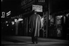 Rear view of man in long coat walking towards passport photo shop stock video