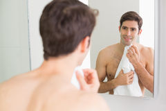 Rear view of man looking at self in bathroom mirror Stock Photography
