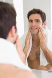 Rear view of a man looking at self in bathroom mirror Stock Images