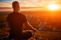 Rear view of the man meditating yoga in lotus pose on the rock at sunset. Horizontal photo. Beautiful landscape with sky and clouds like a background. Concept Stock Images