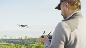Man operating a drone quadrocopter with camera. Rear view of a man operating a drone quad copter with onboard digital camera stock video