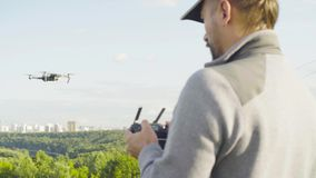 Man operating a drone quadrocopter with camera. Rear view of a man operating a drone quad copter with onboard digital camera stock footage