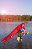 Rear view of man paddling kayak in lake with woman in background. Couple kayaking in lake on a sunny day. Royalty Free Stock Photography