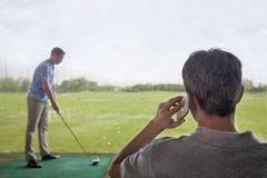 Rear view of man on the phone while another man plays golf in the background Royalty Free Stock Images