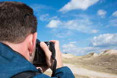 Rear view of a man photographying landscape with digital camera. Rear view of a photographer taking pictures of sand and sky landscape on sunny day Stock Photos