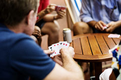 Rear view of man playing card game with friends Stock Images