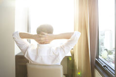 Rear view of man relaxing on chair in the room Stock Images