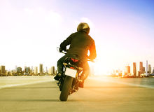 Rear view of man riding motorcycle on urban traffic road for people leisure traveling theme royalty free stock photo