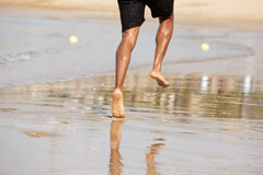 Young man running barefoot on beach. Rear view of man running barefoot on beach Stock Images