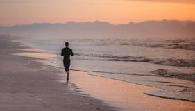 Runner training on the beach in morning. Rear view of man running on the beach in morning. Male athlete on morning run outdoors on seashore Stock Images