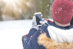 Close up of man using smartphone touch screen. Winter scene. royalty free stock image