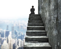 Rear view of man sitting on top of concrete stairs Royalty Free Stock Image