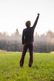 Rear view of a man standing in green meadow with one arm lifted Royalty Free Stock Photography