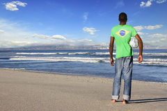 Rear view of man standing wearing Brazilian t shirt with football on a beach Royalty Free Stock Photos