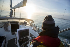 Rear View Of Man Steering Yacht At Helm Stock Images