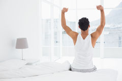 Rear view of a man stretching arms in bed Royalty Free Stock Photo
