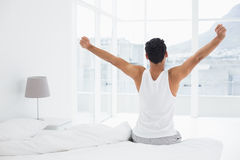 Rear view of a man stretching arms in bed Stock Photo