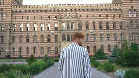 Rear view of the man in striped jacket walking to the old building and touching his red curly hair. stock footage