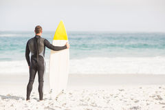 Rear view of man with surfboard standing on the beach Royalty Free Stock Photography
