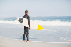 Rear view of man with surfboard standing on the beach Stock Photo