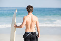 Rear view of man with surfboard standing on the beach Stock Photos
