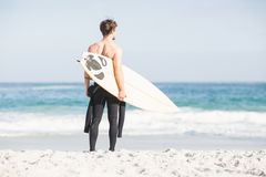 Rear view of man with surfboard standing on the beach Royalty Free Stock Photos