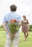 Rear view man surprising woman with bouquet in park Stock Photography